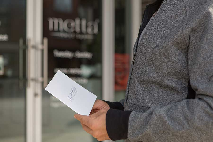 man holding a gift certificate out front of metta rest spa